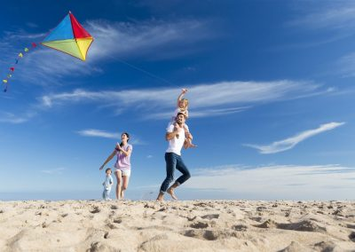 family kite flying on beach