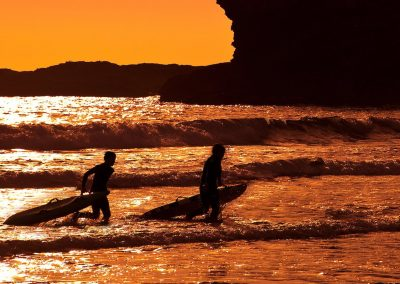 surfers at sunset mawgan porth